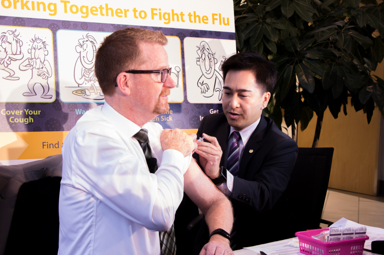BCPhA Vice-President Alex Dar Santos administers a flu shot to BC Minister of Health Terry Lake